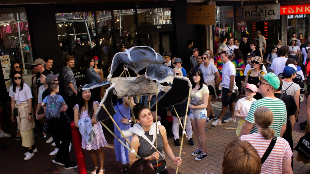 Amy Atkins puppeteering a full size Leatherback Turtle puppet on Cuba Street. The Turtle is suspended in the air above Amy's head.