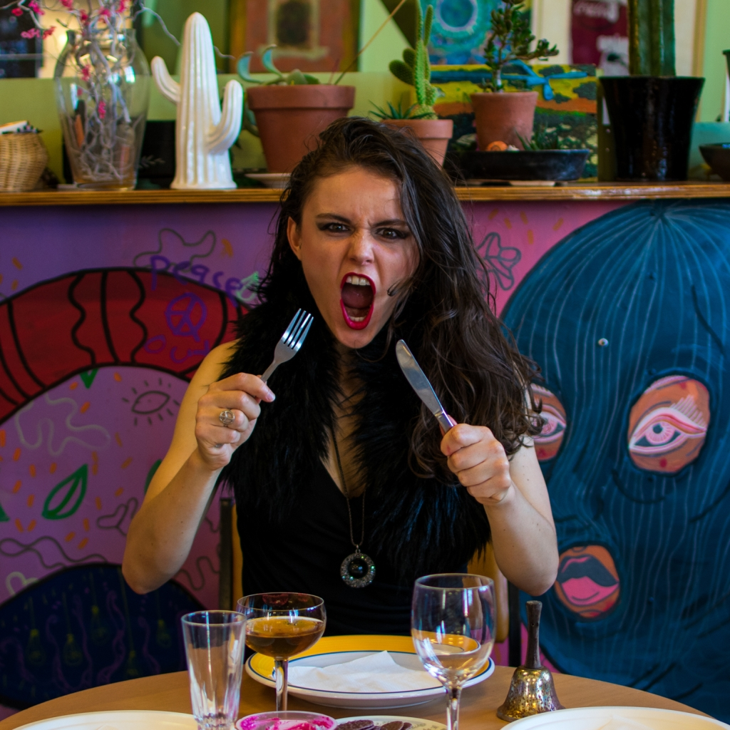 Anastasia Novikov grimacing with her mouth open wide holding a knife and fork up to her mouth.